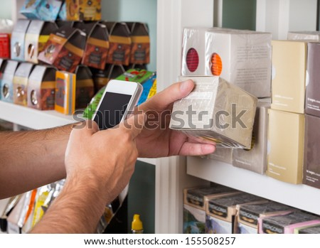 Cropped image of man's hand scanning product through mobile phone - stock photo