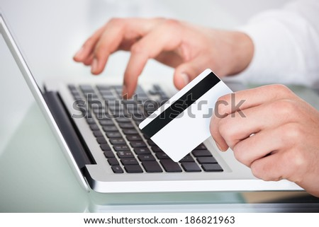 Cropped image of man shopping with credit card and laptop - stock photo