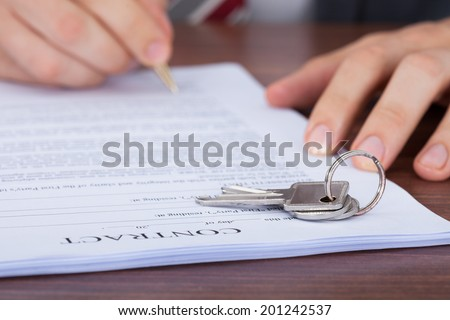 Cropped image of man signing contract with keys on it - stock photo
