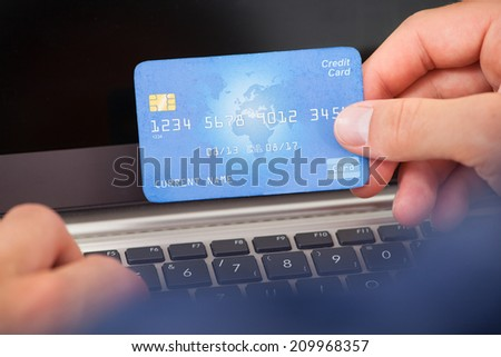 Cropped image of man using credit card and laptop to shop online - stock photo