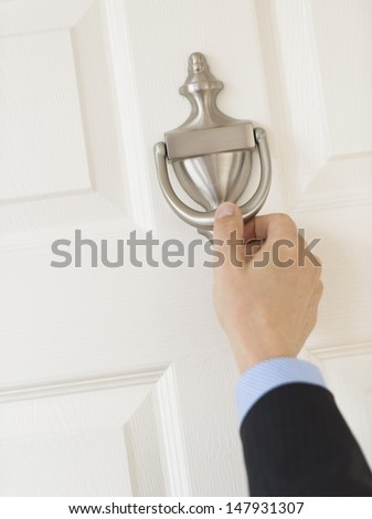 Cropped image of mature businessman's hand knocking door handle - stock photo