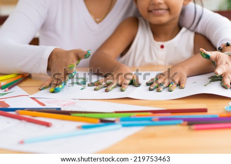 Cropped image of mother and daughter doing fingerprints, selective focus - stock photo