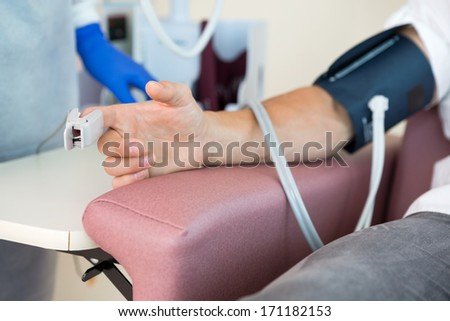 Cropped image of oximeter attached to male patient's finger in hospital room - stock photo