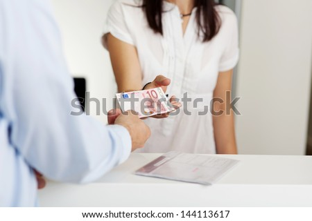 Cropped image of patient paying money to receptionist in dentist clinic - stock photo