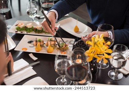 Cropped image of people eating appetizers at the restaurant - stock photo
