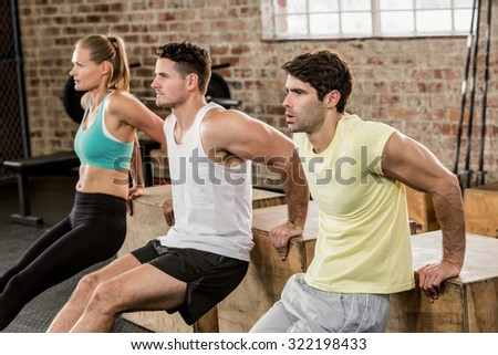 Cropped image of people holding plyo box and exercising at the gym - stock photo