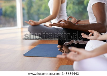 Cropped image of people meditating in lotus position - stock photo