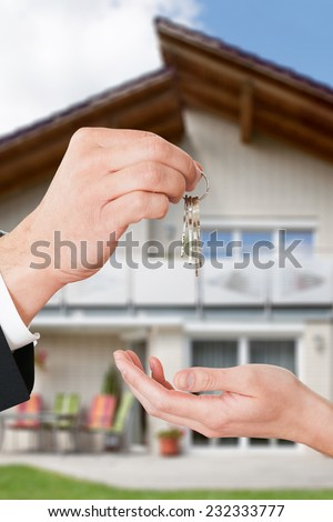Cropped image of real estate agent giving keys to owner against new house - stock photo