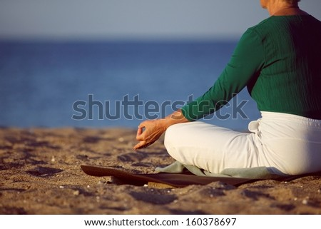 Cropped image of senior woman in meditation on sandy beach. Elderly woman sitting on the beach in lotus pose doing relaxation exercise . Mature woman doing yoga - stock photo