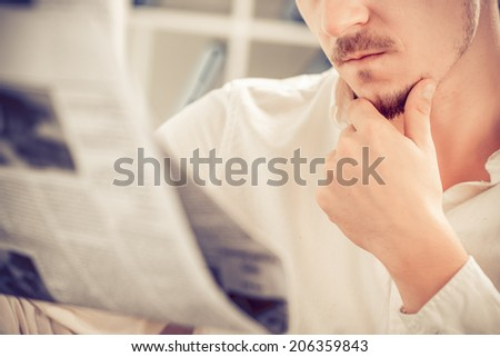 Cropped image of serious man reading newspaper - stock photo