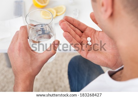 Cropped image of sick young man taking tablets with glass of water at home - stock photo