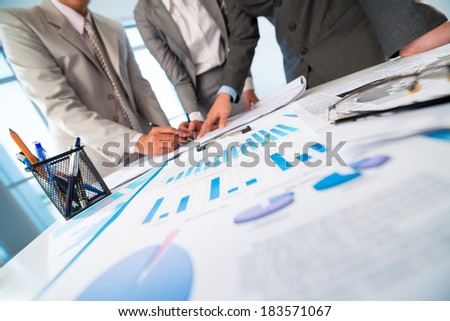 Cropped image of team making business plan on the foreground  - stock photo