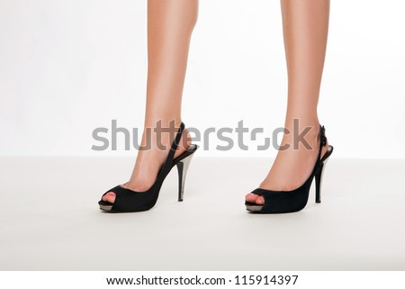 Cropped image of the beautiful shapely smooth legs of a woman in stylish black leather stilettoes with open toes and straps - stock photo