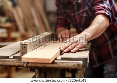 Cropped image of the hands of a skilled craftsman cutting a wooden plank with a circular saw in a workshop - stock photo