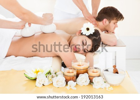 Cropped image of therapist massaging woman's back with herbal compress stamps at spa - stock photo