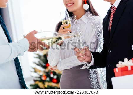 Cropped image of waiter pouring champagne into a flute at the Christmas party - stock photo