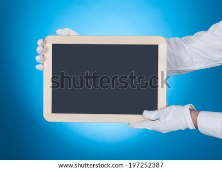 Cropped image of waiter showing digital tablet over blue background - stock photo