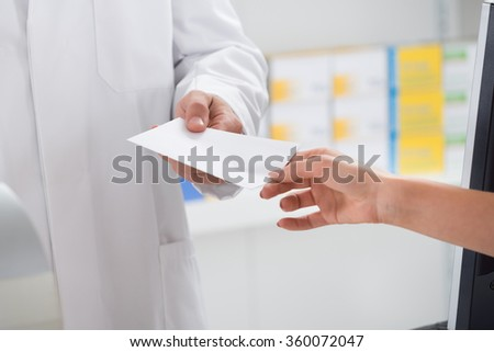 Cropped image of woman giving prescription paper to pharmacist in store - stock photo
