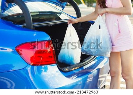 Cropped image of woman putting shopping bags inside trunk of her blue car, on a mall, store, supermarket parking lot - stock photo