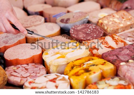 Cropped image of woman's hand picking up meat with fork in supermarket - stock photo