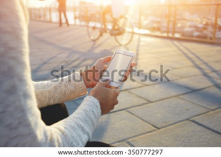 Cropped image of woman's hands holding smart phone with blank copy space screen for your text message or promotional content, female chatting in network on cell telephone while sitting near sea port  - stock photo