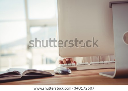 Cropped image of woman typing on keyboard in her office - stock photo