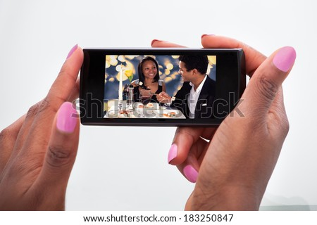 Cropped image of woman watching video on mobile phone at home - stock photo