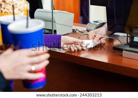 Cropped image of women holding drinks while buying movie tickets from seller at box office - stock photo