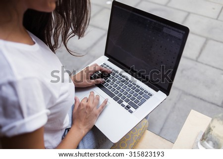 Cropped image of women's hands keyboarding on her laptop computer while sitting in restaurant in the fresh air,young female using net-book with blank copy space screen for your text message or content - stock photo