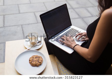 Cropped image of women's hands keyboarding on net-book with blank copy space screen for your text message or content, female student work on laptop typing text during breakfast in modern coffee shop - stock photo