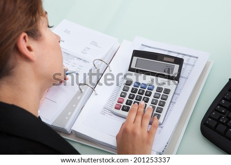 Cropped image of young businesswoman calculating bills at desk in office - stock photo