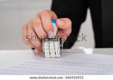 Cropped image of young businesswoman stamping contract paper at office desk - stock photo