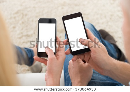 Cropped image of young couple using smart phones with blank screens at home - stock photo