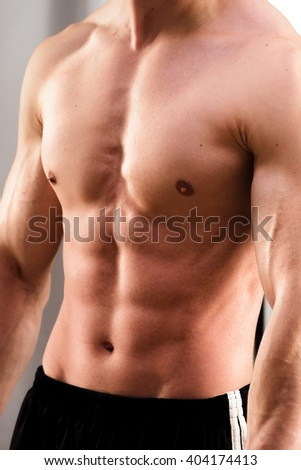 Cropped image of young fit man in sweatpants flexing ab - stock photo