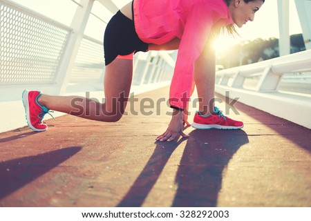 Cropped image of young fit woman in tracksuit took the position in preparation for her morning intense jog outdoors, sporty girl dressed in bright sportswear ready to start the run outside in evening - stock photo