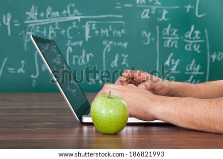 Cropped image of young male student solving math's problem on laptop by green apple on table - stock photo
