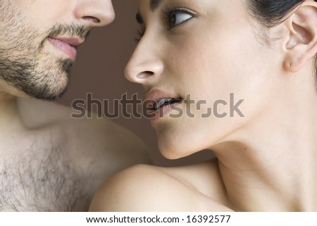 Cropped image of young man staring into the face of young woman - stock photo