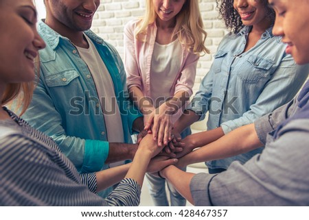 Cropped image of young people of different nationalities holding hands together and smiling - stock photo