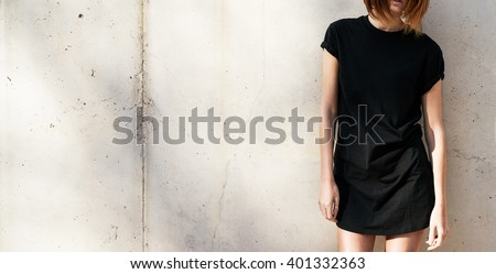 Cropped image on a stylish young woman dressed in a black blank t-shirt standing against a background of a concrete wall in the rays of the setting sun - stock photo