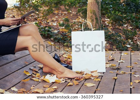 Cropped image on a young beautiful woman making online purchases during the lunch break while sitting in the park.standing next to a white blank paper bag for your text or design - stock photo