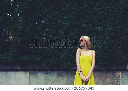 Cropped image with lovely young woman in summer bright dress posing on nature fence background in city, female cute hipster girl standing against blank copy space for text message or content, filter - stock photo