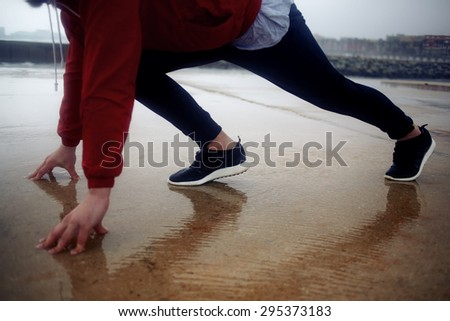 Cropped image with male runner in preparing position ready to start morning intense jog on shoreline, sportsman in windbreaker standing on runway start at cloudy raining day at wet asphalt,thought fog - stock photo