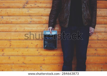 Cropped image with stylish young man holding blank digital tablet while standing on wooden background with big copy space area for text message or content, male hipster hand holding touch pad, filter - stock photo