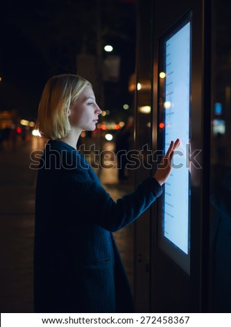 Cropped image with young beautiful woman touching big digital screen of smart bus stop in Barcelona, female using city computer for touristic information while standing at night with urban lights - stock photo