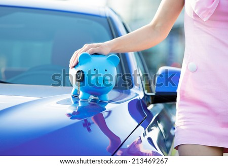 Cropped image woman customer, agent and new car, piggy bank, key on hood, isolated outside, outdoors. Dealership offering credit line, finance services. Lease, automobile purchase, financing concept - stock photo