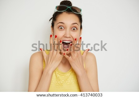 Cropped isolated shot of happy young brunette female wearing bun and yellow top, looking and screaming with excitement and joy at the camera. Beautiful girl posing against white studio background - stock photo