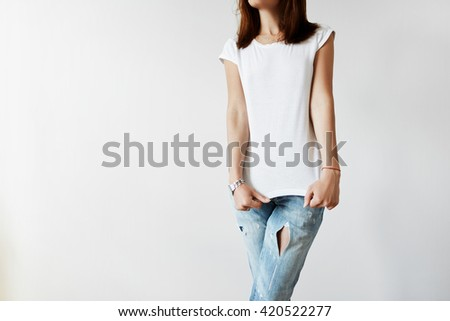 Cropped isolated shot of young female model in trendy ripped denim pants stretching her blank T-shirt. Student girl dressing up before going out for a walk with her boyfriend after classes at college - stock photo