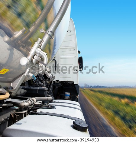 Cropped, motion-blurred close-up of semi on the road. No people are viewable in the shot. Square framed shot. - stock photo