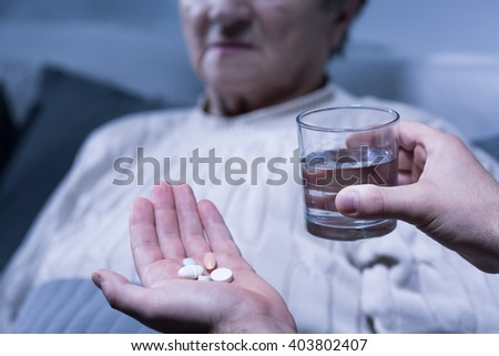 Cropped picture of a person holding some pills and a glass of water - stock photo