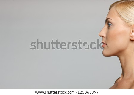 Cropped picture of side view closeup of beautiful blond woman looking forward over gray background - stock photo